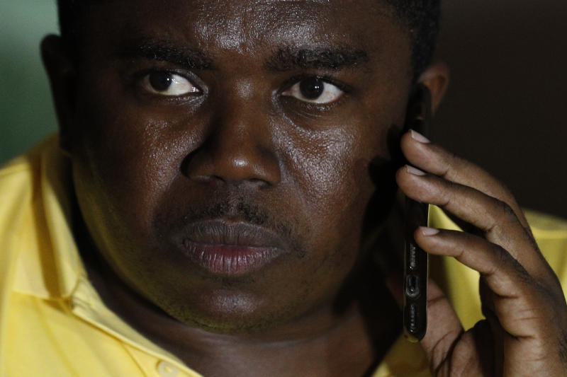 André Michel speaks on a cell phone at the start of a press conference to announce plans for a massive protest march to the United Nations headquarters the following day, in Port-au-Prince, Haiti, Thursday, Oct. 3, 2019. Among those leading the protests is an opposition coalition called the Democratic and Popular Sector, whose members include attorney Michel, one of 70 candidates who ran in the 2015 presidential elections.(AP Photo/Rebecca Blackwell)