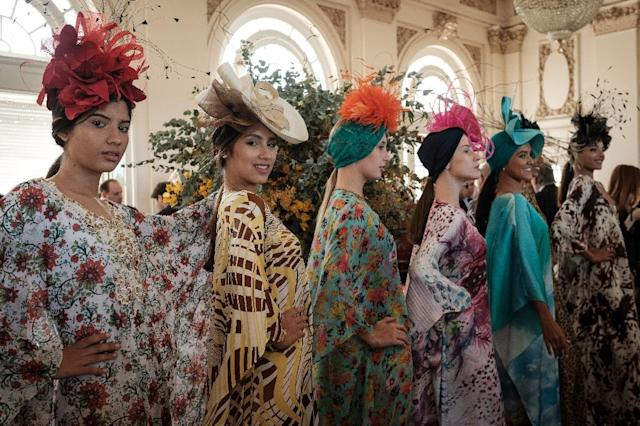 Models display hats created by Denis Linhares to exclusive members of the Jockey Club hippodrome waiting at the Salao das Rosas, or Roses Room, for the Grande Premio Brasil, Brazil's biggest horse race of the year, in Rio de Janeiro (AFP Photo/Yasuyoshi CHIBA)