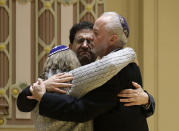 FILE - In this Oct. 28, 2018 file photo, Rabbi Jeffrey Myers, right, of Tree of Life/Or L'Simcha Congregation hugs Rabbi Cheryl Klein, left, of Dor Hadash Congregation and Rabbi Jonathan Perlman during a community gathering held in the aftermath of a deadly shooting at the Tree of Life Synagogue in Pittsburgh. Perlman took shelter in a supply closet with three members of his New Light congregation during the attack. (AP Photo/Matt Rourke, File)