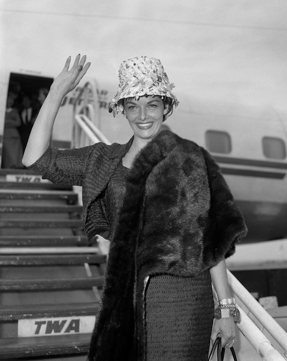 <p>Actress Jane Russell sported a chic airport look as she departed from London, decked out in a fur coat, ornate hat, and several bracelets. Is this why it's called a runway?<br></p>