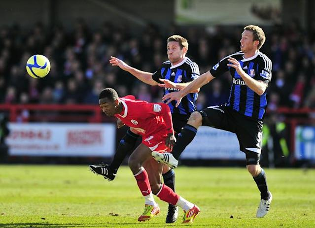 "Crawley Town's midfielder Sanchez Watt (C) vies with Stoke City's defender Matthew Upson (L) and Welsh defender Danny Collins (R) during their FA Cup fifth round football match against Stoke City at Broadfield Stadium in Crawley on February 19, 2012. RESTRICTED TO EDITORIAL USE. No use with unauthorized audio, video, data, fixture lists, club/league logos or ""live"" services. Online in-match use limited to 45 images, no video emulation. No use in betting, games or single club/league/player publications. (Photo by Glyn Kirk/AFP/Getty Images)"