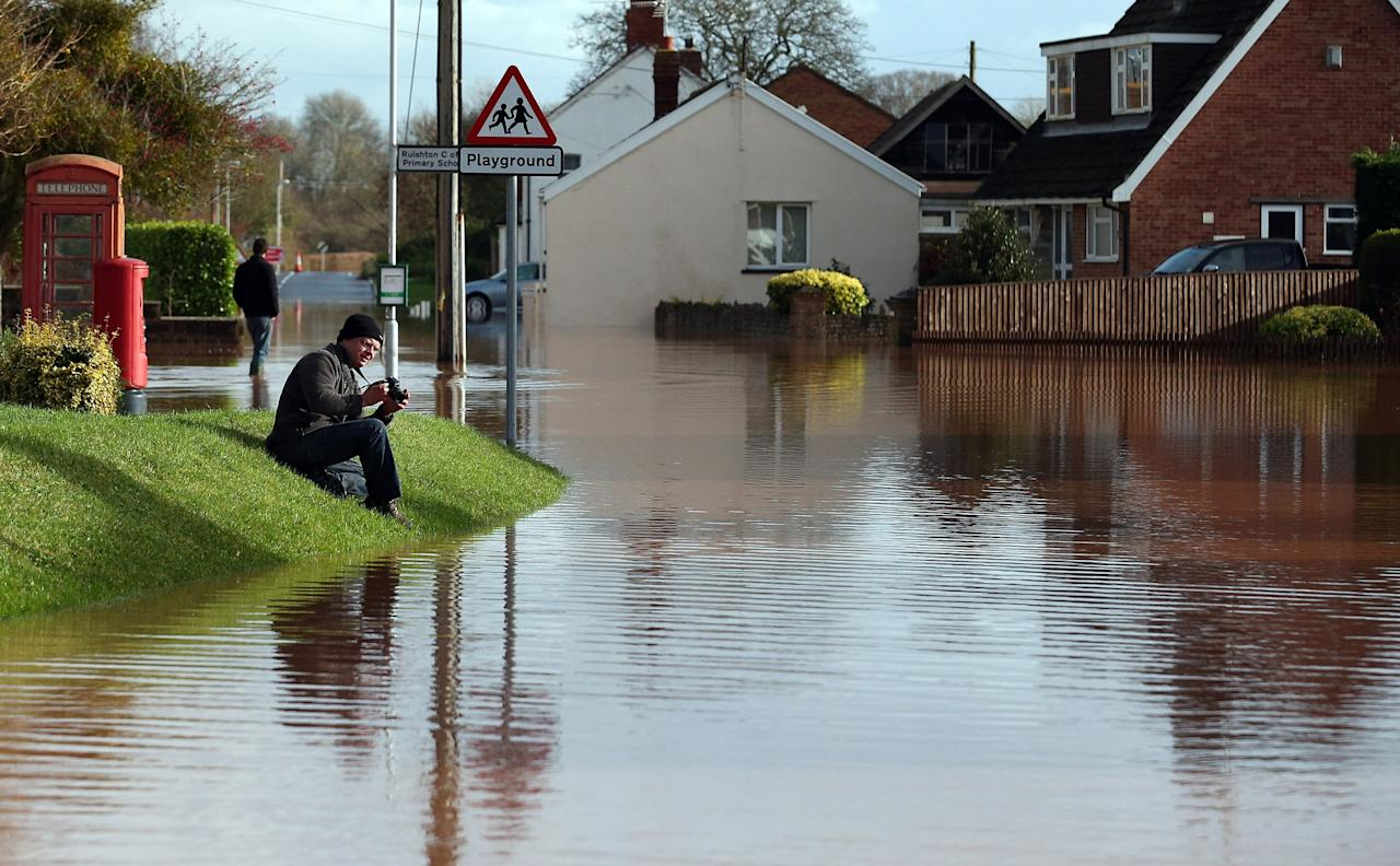 TAUNTON, UNITED KINGDOM - NOVEMBER 25:  A man takes a photograph of flood water in the centre of the village of Ruishton, near Taunton, on November 25, 2012 in Somerset, England. Another band of heavy rain and wind continued to bring disruption to many parts of the country today particularly in the south west which was already suffering from flooding earlier in the week.  (Photo by Matt Cardy/Getty Images)