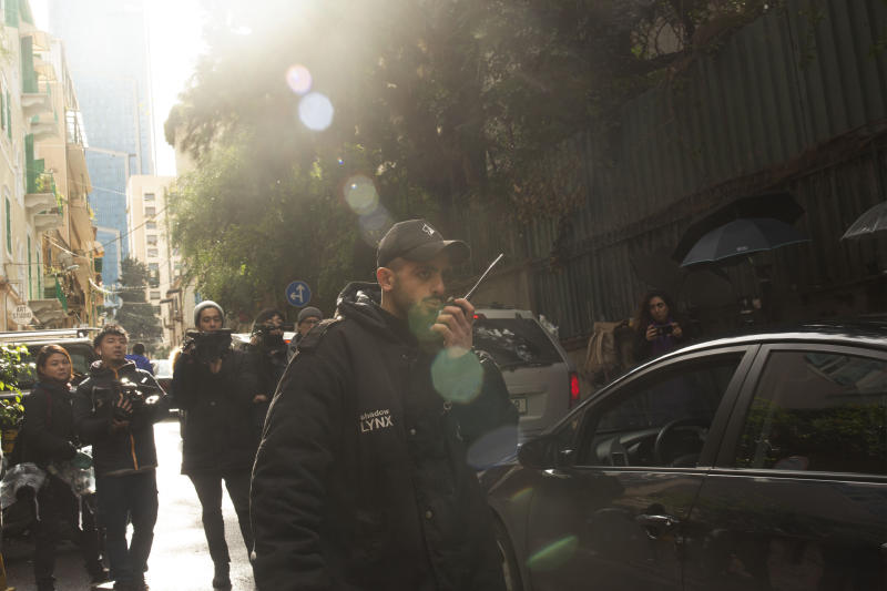 A private security guard speaks on a radio as a vehicle approaches the house of ex-Nissan chief Carlos Ghosn in Beirut, Lebanon, Saturday, Jan. 4, 2020. Ghosn earlier this week jumped bail in Japan and fled to Lebanon rather than face trial on financial misconduct charges in a dramatic escape that has confounded and embarrassed authorities. (AP Photo/Maya Alleruzzo)