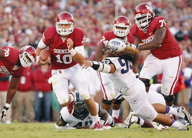 Oklahoma quarterback Blake Bell (10) runs for a first down in front of TCU's Michael Mosharrafa during the first half of an NCAA college football game on Saturday, Oct. 5, 2013, in Norman, Okla. (AP Photo/Alonzo Adams)