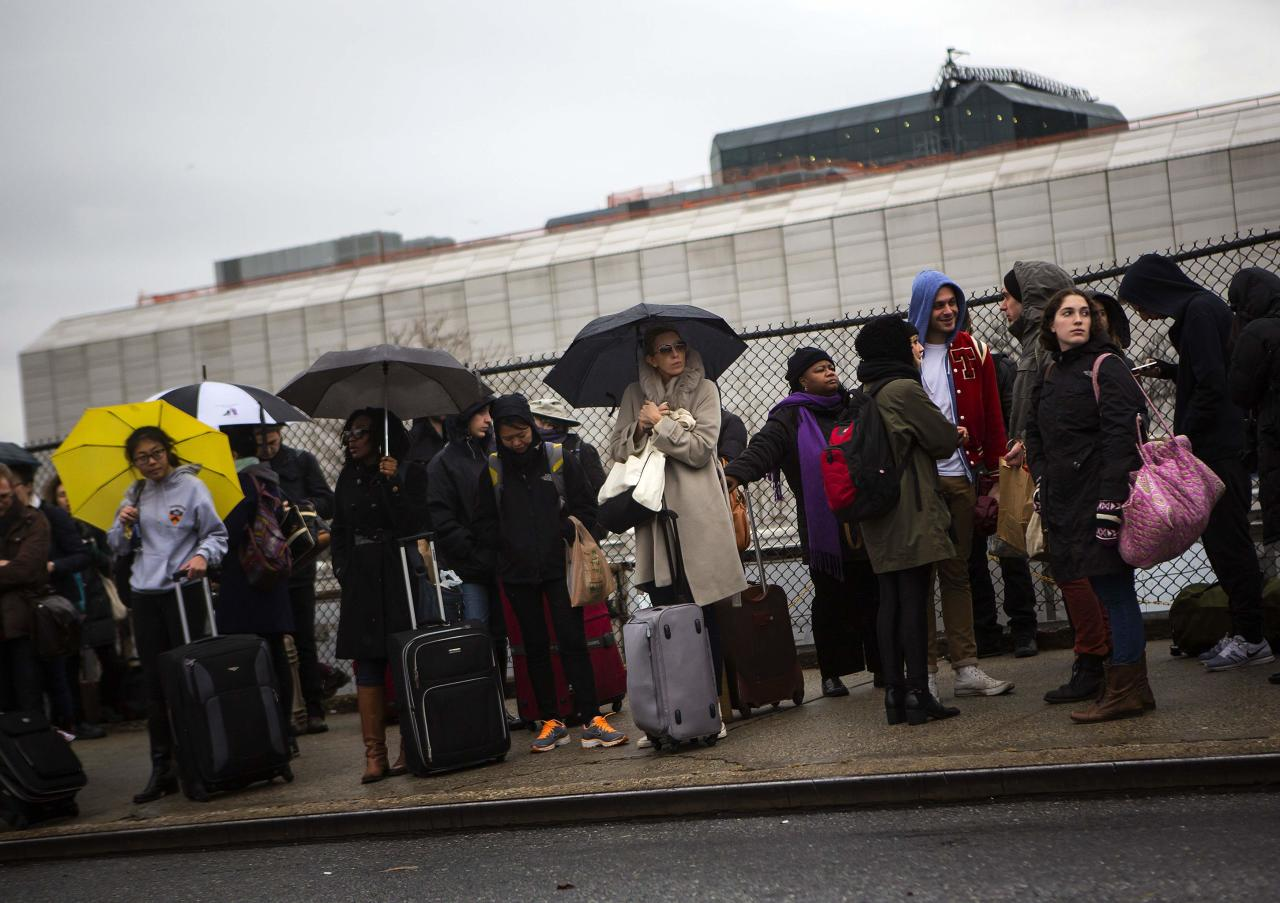 Travelers wait to board a bus in New York November 27, 2013. A wintry blast of heavy rain, wind and snow across the eastern United States disrupted Thanksgiving trip plans on Wednesday for some of the millions of people hitting the roads and taking to the skies on the busiest holiday travel day of the year. REUTERS/Eric Thayer (UNITED STATES - Tags: ENVIRONMENT TRANSPORT)