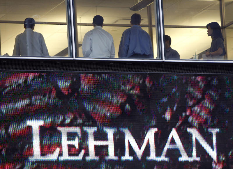 People stand next to windows above an exterior sign at the Lehman Brothers headquarters in New York in this September 16, 2008 file photo. September 14, 2009 marks the one year anniversary of the bankruptcy filing of Lehman Brothers. Picture taken September 16, 2008. REUTERS/Chip East/Files (UNITED STATES BUSINESS EMPLOYMENT ANNIVERSARY)