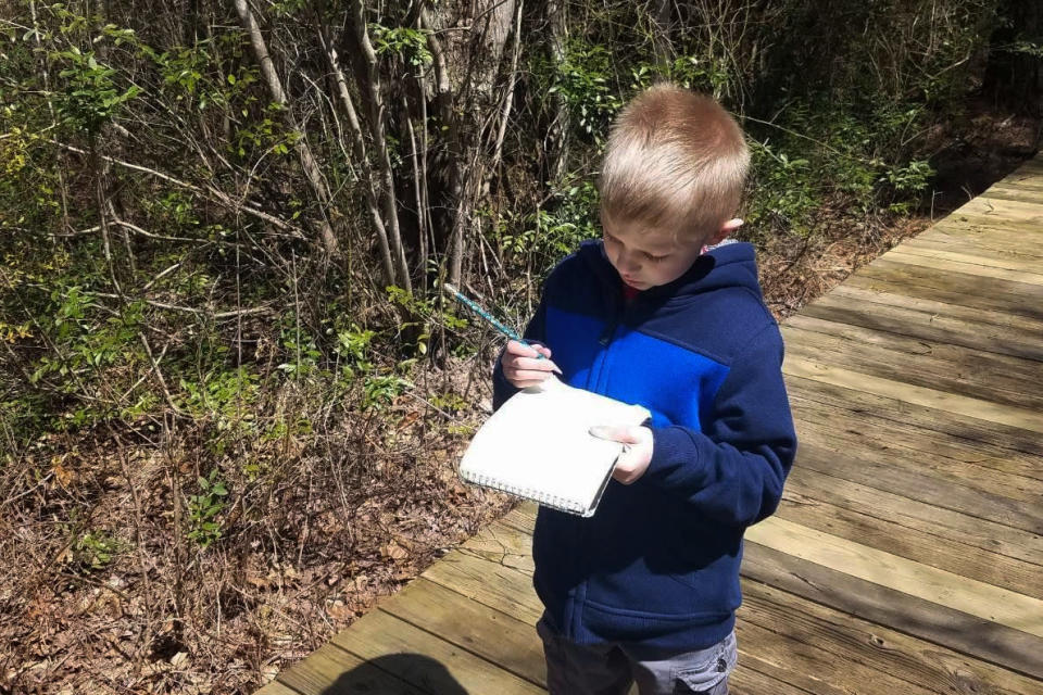 In this April 16, 2020, photo, provided by Dan Cappilla, his son Gavin takes notes for a school project while walking on a nature trail in Tuckerton, N.J. The coronavirus pandemic has created a staggering child care crisis that threatens to undermine the reopening of the U.S. economy. Dan Cappilla saw other no choice but to take unpaid leave from his job as an overnight baker at a ShopRite in Manahawkin, N.J. (Dan Cappilla via AP)