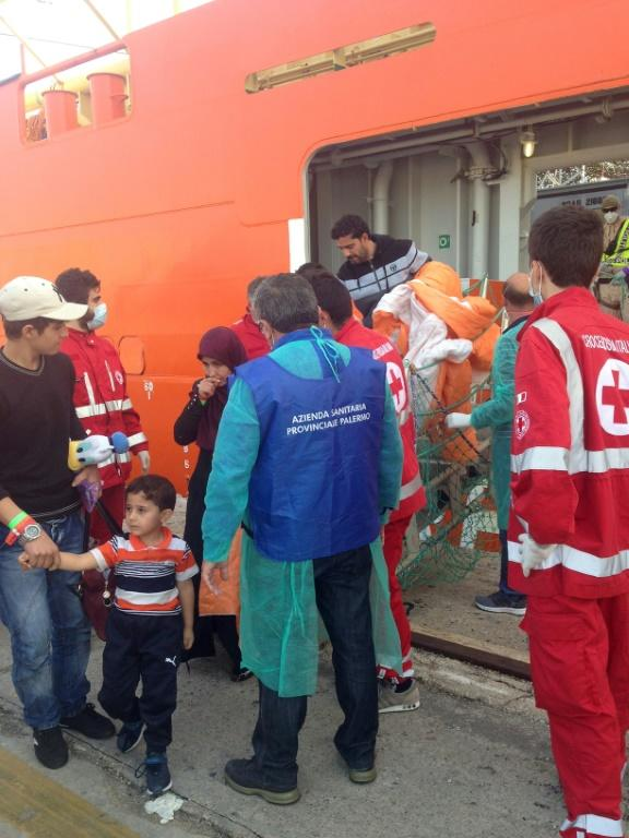 Women and children disembark from the Siem Pilot ship on October 24, 2016 in Palermo after rescue operations of migrants off the coast of Libya three days earlier