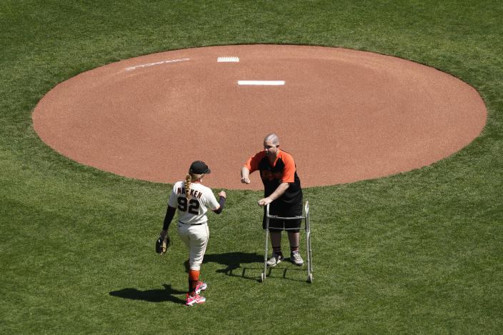 Bryan Stow is greeted by San Francisco Giants assistant coach Alyssa Nakken before throwing out the ceremonial first pitch before a baseball game against the Colorado Rockies, Friday, April 9, 2021, in San Francisco. Ten years ago Stow was attacked at Dodger Stadium. (AP Photo/Eric Risberg)
