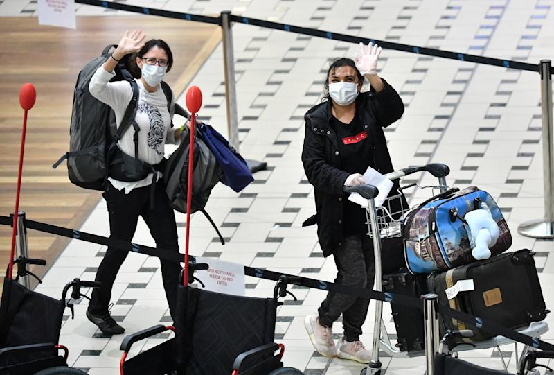 Australians evacuated from South America via a Qantas repatriation flight due to the COVID-19 pandemic are seen after landing at Brisbane International Airport. AAP Image