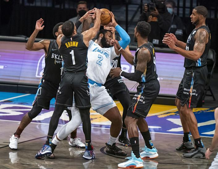 The Lakers' Andre Drummond is defended by several Brooklyn Nets during the first half April 10, 2021.