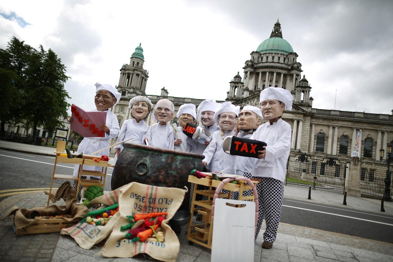 BELFAST, NORTHERN IRELAND - JUNE 16: Oxfam charity volunteers wear masks depicting the G8 leaders during a photocall outside City Hall on June 16, 2013 in Belfast, Northern Ireland. The G8 group of world leaders will meet tomorrow in Fermanagh, Northern Ireland.  (Photo by Peter Macdiarmid/Getty Images)