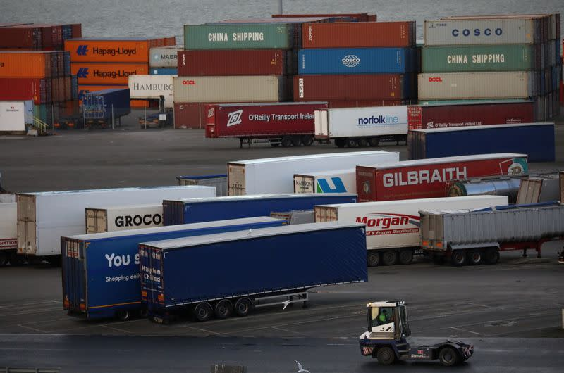 Port vehicle drives past trailers and shipping containers at the Port of Belfast