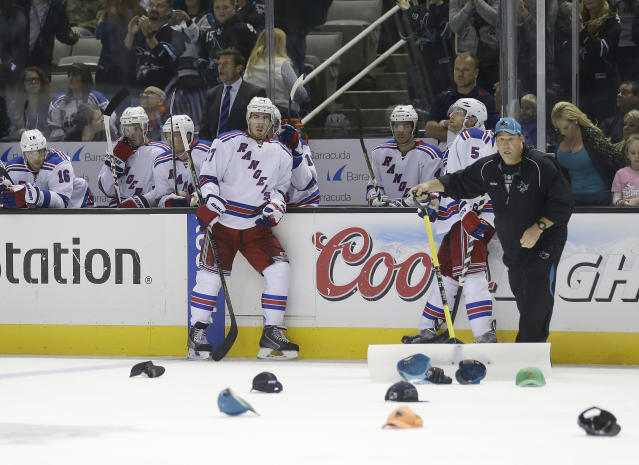 The New York Rangers watch from the sideline as hats thrown on the ice by fans are picked up following San Jose Sharks' Tomas Hertl, of the Czech Republic's third goal of the game during the third period of an NHL hockey game on Tuesday, Oct. 8, 2013, in San Jose, Calif. (AP Photo/Marcio Jose Sanchez)