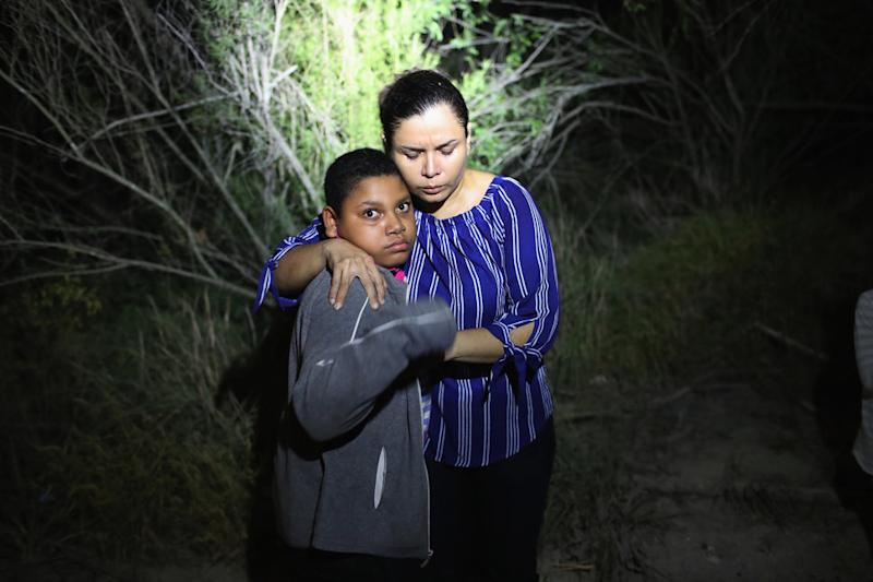 """MCALLEN, TX - JUNE 12: A U.S. Border Patrol spotlight shines on a terrified mother and son from Honduras as they are found in the dark near the U.S.-Mexico border on June 12, 2018 in McAllen, Texas. The asylum seekers had rafted across the Rio Grande from Mexico and had become lost in the woods. They were then detained by Border Patrol agents and then sent to a processing center for possible separation. Customs and Border Protection (CBP) is executing the Trump administration's """"zero tolerance"""" policy towards undocumented immigrants. U.S. Attorney General Jeff Sessions also said that domestic and gang violence in immigrants' country of origin would no longer qualify them for political asylum status. (Photo by John Moore/Getty Images)"""