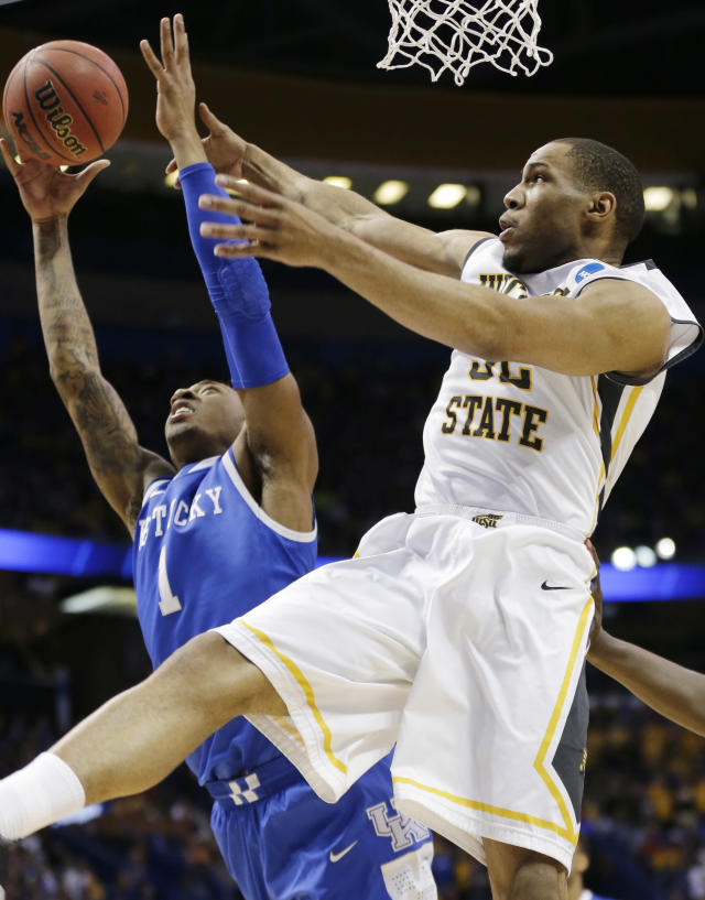 Kentucky guard/forward James Young (1) and Wichita State guard Tekele Cotton (32) go after the ball during the first half of a third-round game of the NCAA college basketball tournament Sunday, March 23, 2014, in St. Louis. (AP Photo/Charlie Riedel)