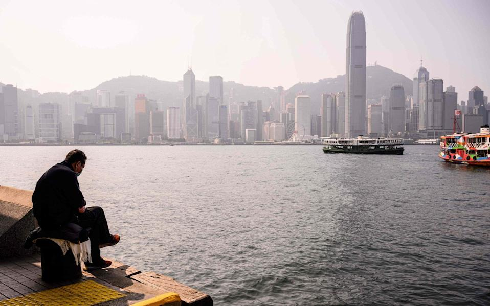 A man on the harbourside in Hong Kong - Anthony Wallace/AFP