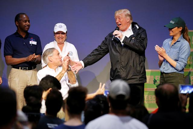 <p>Texas Governor Greg Abbott (L) reacts as President Donald Trump speaks at a church relief center during a visit with flood survivors and volunteers of Hurricane Harvey in Houston, Texas, Sept. 2, 2017. (Photo: Kevin Lamarque/Reuters) </p>