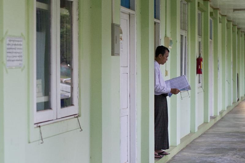 Phyo Min Thein, a Lower House MP for the National League for Democracy reads a newspaper in the doorway of his lodgings in Naypyidaw on August 24, 2015 (AFP Photo/Ye Aung Thu)