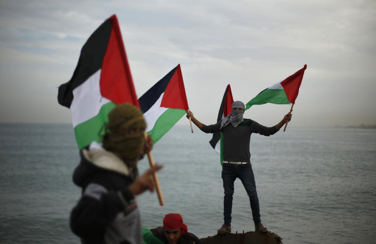 Palestinians wave national flags during a protest against the blockade on Gaza, at the seaport of Gaza City December 2, 2013. Israel imposed a blockade on Gaza in 2007 after Islamist group Hamas seized control of the territory in a brief civil war with Western-backed Palestinian President Mahmoud Abbas's Fatah party. REUTERS/Suhaib Salem (GAZA - Tags: POLITICS CIVIL UNREST)