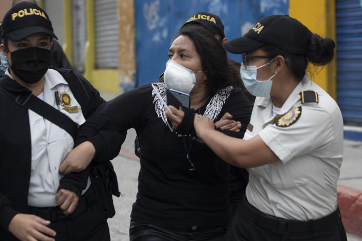 A woman is detained by police near the Congress building after protesters set a part of the building on fire, in Guatemala City, Saturday, Nov. 21, 2020. Hundreds of protesters were protesting in various parts of the country Saturday against Guatemalan President Alejandro Giammattei and members of Congress for the approval of the 2021 budget that reduced funds for education, health and the fight for human rights. (AP Photo/Moises Castillo)