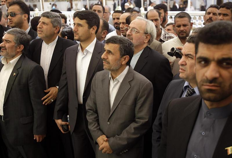 Iranian President Mahmoud Ahmadinejad, center, visits Imam Ali shrine in Najaf, Iraq, Friday, July 19, 2013. Ahmadinejad is in southern Iraq to visit two of the holiest cities for Shiite Muslims amid tight security on the second day of his two-day visit to the country. The outgoing Iranian president waved to worshippers and smiled on Friday morning as he entered the Imam Ali shrine in Najaf, a city 160 kilometers (100 miles) south of Baghdad. (AP Photo/Karim Kadim, Pool)