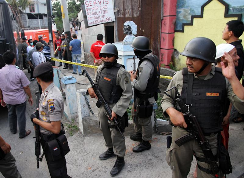 Indonesian police officers stand guard outside a building after a raid in Solo, Central Java, Indonesia, Saturday, Oct. 27, 2012. Indonesian police say they have arrested 11 people suspected of planning a range of terrorist attacks on domestic and foreign targets including the U.S. and Australian embassies. (AP Photo)
