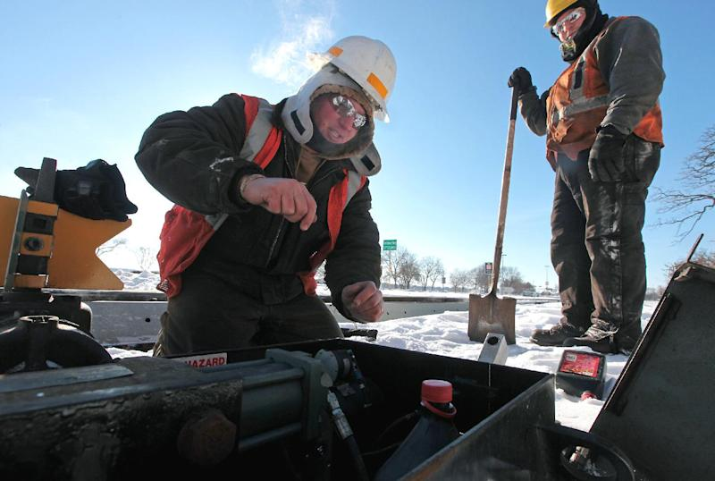 Wisconsin and Southern Railway workers Stacey Hurda, left, and Brady Whipple work to thaw a frozen power switch which controls a track changeout in Madison, Wis., Monday, Jan. 6, 2014. (AP Photo/Wisconsin State Journal, John Hart)