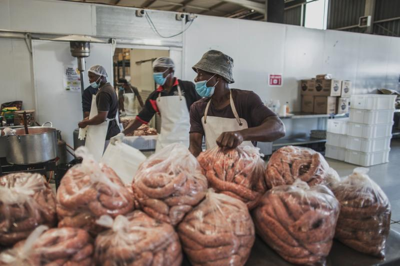 Men in a kitchen in Johannesburg prepare large bags full of uncooked sausages.