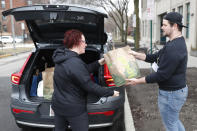 Sugar Beets Food Co-Op employee Jamie Melendy, right, gives curb service to Lola Wright in the Village of Oak Park, Ill., Friday, March 20, 2020. There are at least three confirmed cases of COVID-19 in Oak Park, just nine miles from downtown Chicago, where the mayor has ordered residents to shelter in place. With so few tests available, surely there are others, says Tom Powers, spokesman for the village of about 52,000 in a metropolitan area with millions. (AP Photo/Charles Rex Arbogast)
