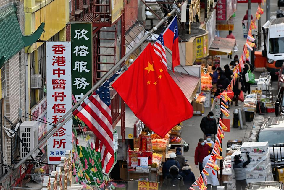 A Chinese flag hangs between American flags in Chinatown on February 17, 2021 in New York City. - No annual parade or large family gatherings greeted the Lunar New Year last week. Just relief at the passing of the Year of Rat and hope that the Year of the Ox will bring a turnaround in fortunes. (Photo by Angela Weiss / AFP) (Photo by ANGELA WEISS/AFP via Getty Images)