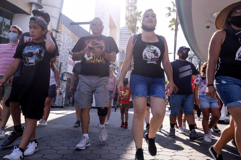 """People arrive at Universal Studios in Universal City, Calif., Tuesday, June 15, 2021. On Tuesday, California lifted most of its COVID-19 restrictions and ushered in what has been billed as the state's """"Grand Reopening."""" (AP Photo/Ringo H.W. Chiu)"""