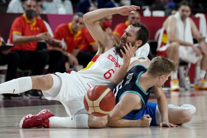 Spain's Sergio Rodriguez (6) and Slovenia's Luka Rupnik (5) fall to the floor during a men's basketball preliminary round game at the 2020 Summer Olympics, Sunday, Aug. 1, 2021, in Saitama, Japan. (AP Photo/Eric Gay)