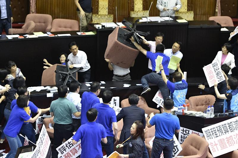 Opposition lawmakers raised large padded office chairs above their heads, surrounding the podium and tussling with rival legislators (AFP Photo/SAM YEH)