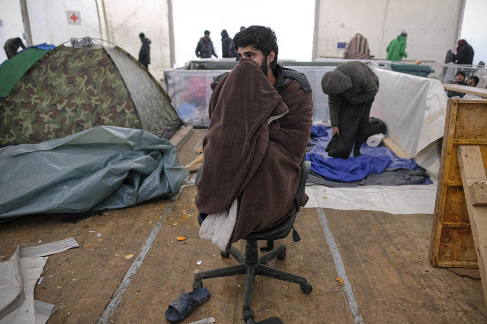 A migrant sits on a chair covered in a blanket in a temporary shelter at the Lipa camp northwestern Bosnia, near the border with Croatia, Saturday, Dec. 26, 2020. Hundreds of migrants are stranded in a burnt-out squalid camp in Bosnia as heavy snow fell in the country and temperatures dropped during a winter spell of bad weather after fire earlier this week destroyed much of the camp near the town of Bihac that already was harshly criticized by international officials and aid groups as inadequate for housing refugees and migrants.(AP Photo/Kemal Softic)
