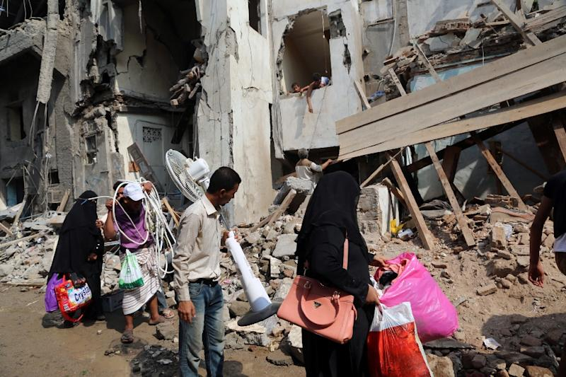 Yemenis carry belongings they recovered from the rubble of buildings destroyed during Saudi-led air strikes the previous day, in the rebel-held Yemeni port city of Hodeida