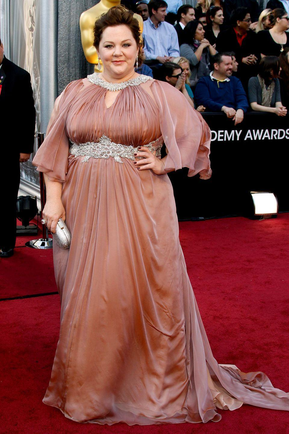 """<p>McCarthy may have been nominated for a Best Supporting Actress Oscar for her hilarious turn in <em>Bridesmaids</em>, but she still couldn't find a designer to dress her for the 2012 Academy Awards. </p><p>""""Two Oscars ago [in 2012], I couldn't find anybody to do a dress for me. I asked five or six designers—very high-level ones who make lots of dresses for people - and they <em>all</em> said no,"""" she told <em><a href=""""http://www.redbookmag.com/fashion/interviews/g787/melissa-mccarthy-interview/?click=list#last-slide"""" rel=""""nofollow noopener"""" target=""""_blank"""" data-ylk=""""slk:Redbook"""" class=""""link rapid-noclick-resp"""">Redbook</a></em>. She eventually walked the red carpet in a draped rose-gold dress by plus-size designer Marina Rinaldi (pictured). </p><p>The experience prompted the comedian—having previously studied clothing and textiles at the Fashion Institute of Technology—to create her own fashion line to help women """"feel good about themselves.""""</p>"""