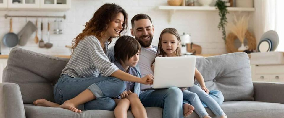Happy young family with small children sitting on sofa in kitchen looking at laptop