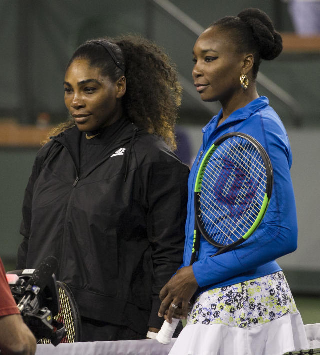 Sisters Serena Williams, left, and Venus Williams, right, meet on the court for a coin toss before their third-round match during the BNP Paribas Open tennis tournament at the Indian Wells Tennis Garden in Indian Wells, Calif., Monday, March 12, 2018. (AP Photo/Crystal Chatham)