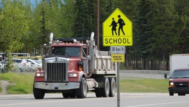 A heavy truck rolls past Holy Family Catholic Elementary School in Whitehorse which is slated to see improvements related to road safety.  (Philippe Morin/CBC - image credit)