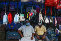 Face masks hang at a roadside stall for sale in Kolkata, India, Friday, Aug. 14, 2020. India's coronavirus death toll overtook Britain's to become the fourth-highest in the world with another single-day record increase in cases Friday. (AP Photo/Bikas Das)
