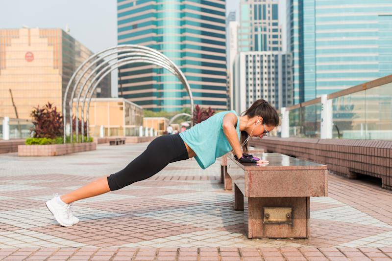 Fitness woman doing feet elevated push-ups on a bench in the city. Sporty girl exercising outdoors.