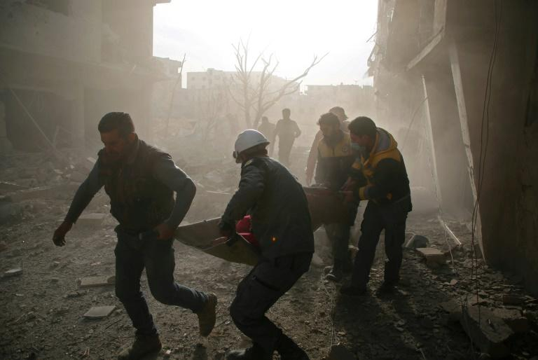 White Helmets evacuate a victim of an air strike in the rebel-held enclave of Eastern Ghouta in Syria