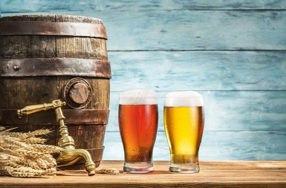 Two glasses of beer sitting next to a barrel and tap