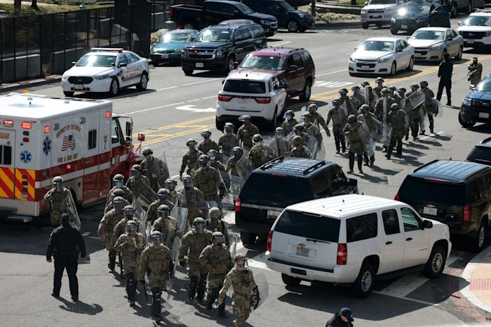 National Guard troops carrying riot shields walk up Constitution Ave. after a vehicle charged a barricade at the U.S. Capitol