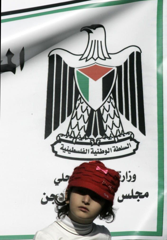 A Palestinian girl stands in front of a Palestinian Authority symbol during a rally supporting the Palestinian UN bid for observer state status, in the West Bank city of Nablus, Thursday, Nov. 29, 2012. The Palestinians are certain to win U.N. recognition as a state on Thursday but success could exact a high price: delaying an independent state of Palestine because of Israel's vehement opposition.(AP Photo/Nasser Ishtayeh)