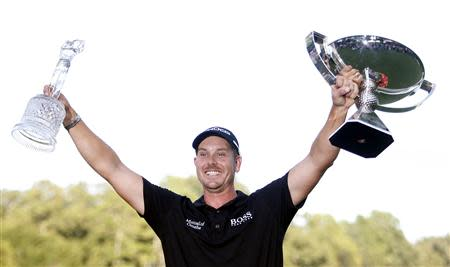 Stenson of Sweden holds up the trophy for winning the the Tour Championship golf tournament and the FedExCup trophy in Atlanta