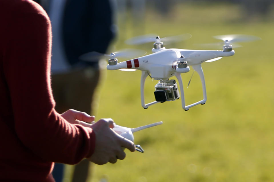 A pilot flies a Phantom drone by DJI company at the 4th Intergalactic Meeting of Phantom's Pilots (MIPP) in an open secure area in the Bois de Boulogne, western Paris, March 16, 2014. Drone operators in France are required to complete a training course to fly an unmanned aerial vehicle and also receive written approval for flights in urban areas. Picture taken March 16, 2014.   REUTERS/Charles Platiau (FRANCE - Tags: SCIENCE TECHNOLOGY)