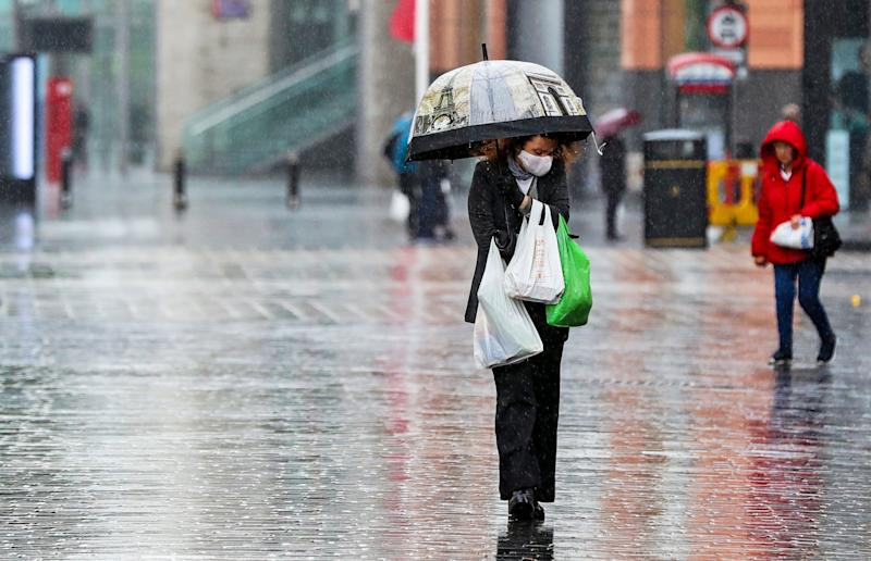 A shopper walks through the rain with an umbrella after a change in the weather has seen the mini heatwave come to an end: PA
