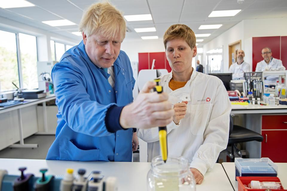 Britain's Prime Minister Boris Johnson (1st-L) visits to the Mologic Laboratory in the Bedford technology Park, north of London on March 6, 2020. - The Prime Minister pledged a further £46 million for research into a coronavirus vaccine and rapid diagnostic tests during the visit to the Laboratory, where British scientists are working on ways to diagnose coronavirus. (Photo by Jack Hill / POOL / AFP) (Photo by JACK HILL/POOL/AFP via Getty Images)
